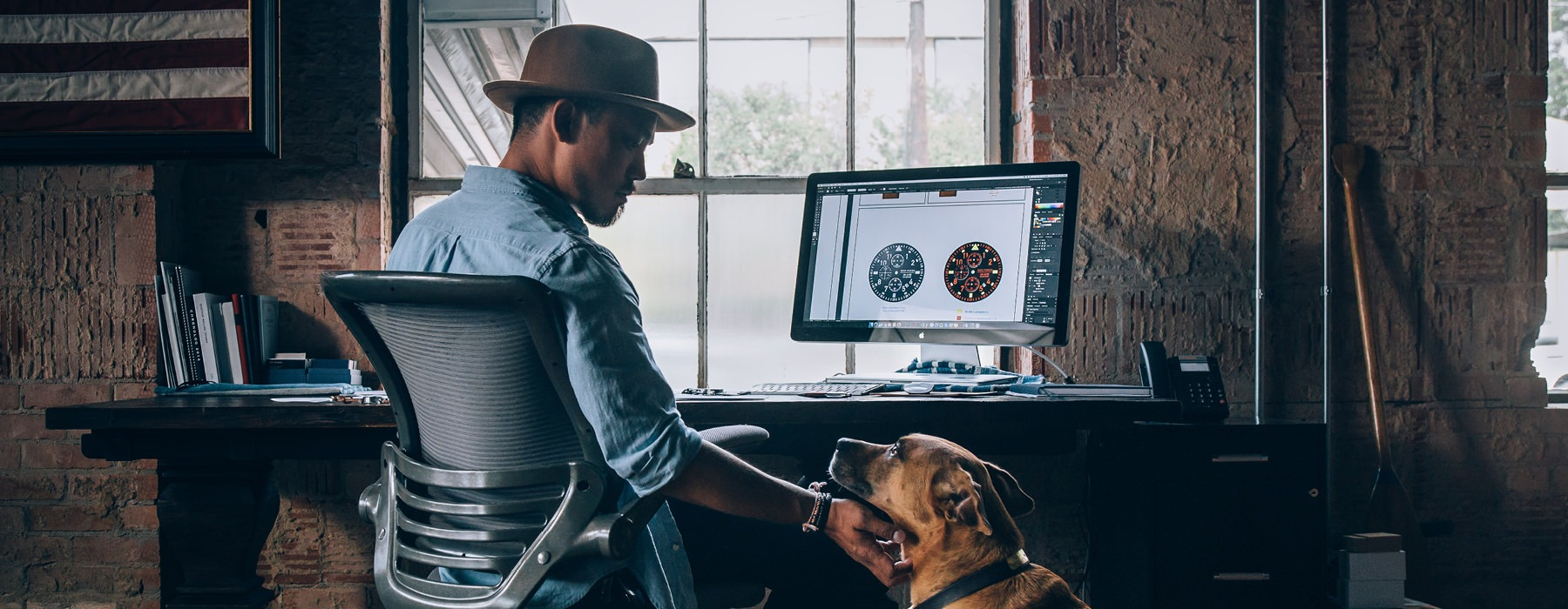 young man with at hat, sits at his desk and scratches his dog's neck as they look at each other